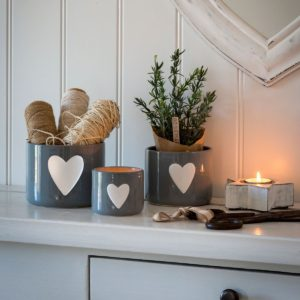 A set of grey plant pots with lovely white hearts on the front of them
