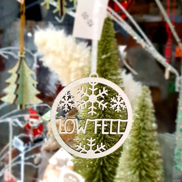 A circular laser cut wooden tree decoration in metallic silver. With beautiful snowflakes and the words Low Fell.