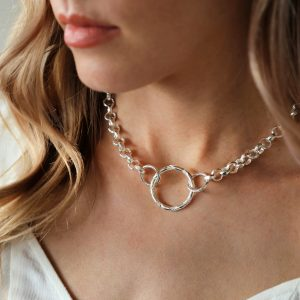 A statement silver plated necklace with a thick chain holding a silver texture hoop.