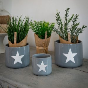 A set of three grey ceramic pots with white stars painted on them.