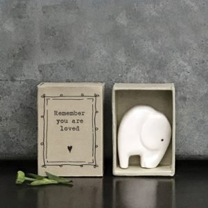 A sweet little ceramic elephant keepsake stored in a little cardboard matchbox with the words 'Remember you are Loved' printed on it.