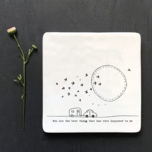A white square coaster with an image of a caravan with birds and the sun in the sky