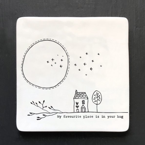 A white square coaster with an image of a house and the moon and birds in the background.