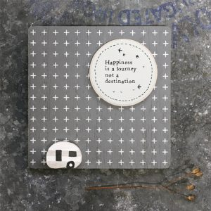 A cute little sign with a dark grey background and a little caravan on it with a large sun and the words 'Happiness is a journey and not a destination.'
