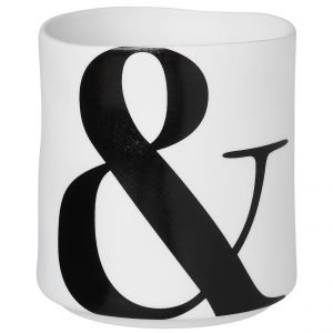 A white porcelain t light holder with a black ampersand