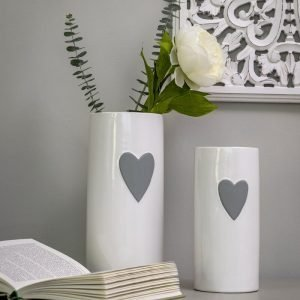 A tall cylindrical white ceramic flower vase with a grey hand painted heart