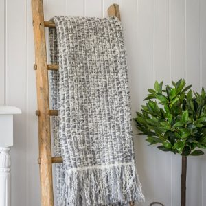 A two tone grey soft throw with fringed edge