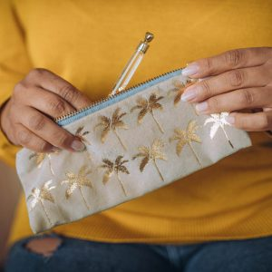 A cream coloured pouch which has gold palm trees printed all over it. The pouch has a brass zip and a velvet tag fastener.