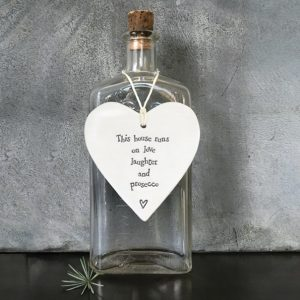 A cream hanging heart from homeware company East of India printed with the wording 'This house rins on love laughter and prosecco.'