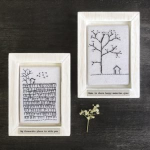 A sweet wooden frame with a square of felt which is embroidered with an image of a field with a tree and a little house. The wording 'My favourite place is with you' printed on it.