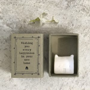 A little porcelain house keepsake which is presented in a cardboard matchbox which has the wording 'Wishing you every happiness in your new home' printed on it.
