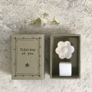 A sweet little white ceramic flower in a pot keepsake in a cardboard matchbox with the words 'Thinking of You' printed on it.