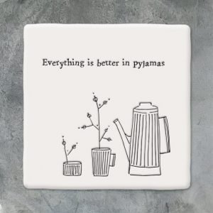 A white square ceramic coaster with an image of a coffee pot and planys and the wording 'Everything is better in pyjamas.' printed on it.