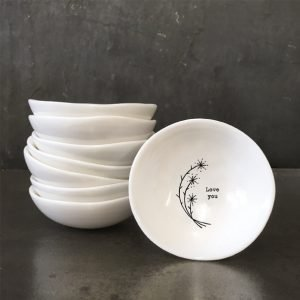 A white ceramic dish from design company East of India with a flower design and the words 'Love You' imprinted in the middle of it.