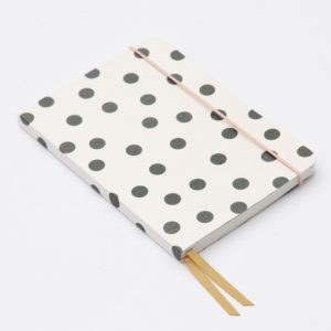 An A5 white and black spotty book with a gold closure ribbon with lined pages from British designer Caroline Gardner