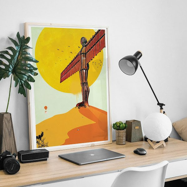 An A3 print of the Angel of the North with a yellow and orange background from artist Em Grafique