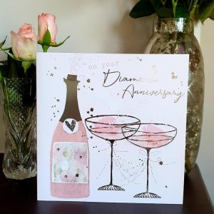 A large square diamond wedding anniversary card with a bottle of champagne and glasses in pinks and silver foil and little crystals
