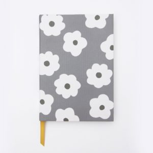 A fantastic lined notebook that is larger than usual with a beautiful white daisy design and grey background, from British design company Caroline Gardner.