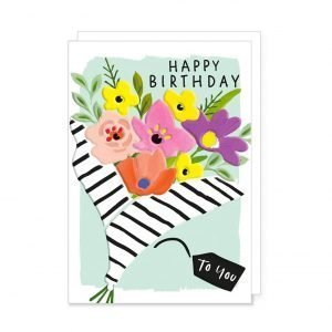 A colourful bouquet of flowers wrapped in black and white stripy paper on a pale blue background and the words Happy Birthday to you