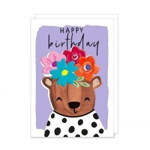 A colourful birthday card with a lilac background, a bear in a black and white spotty top and flowers on it's head and the words Happy Birthday