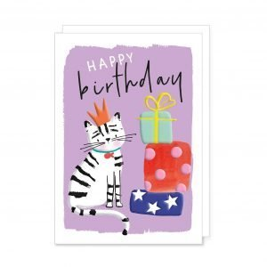 A vibrant and colourful birthday card with a cute black and white stripy cat in a crown sitting next to a pile of colourfully wrapped presents with the words happy birthday