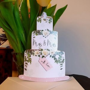 A cut out card in the shape of a tiered wedding cake with lined reverse to write your message and a hanging ribbon. The front of the cake has Mrs & Mrs and a little tag saying with love. Comes with a crisp white envelope.