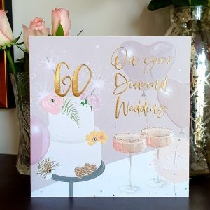 A large luxury 60th golden wedding anniversary card with a cake and champagne glasses, embellished with clear crystal gem stones and gold foiled lettering with a large 60 on top of the cake and the words On Your Diamond Wedding