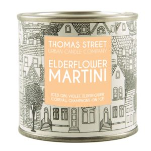 A Thomas Street tin candle with a black and white label but with a peach square in the centre of it. Elderflower Martini aroma
