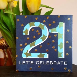A blue card with a big pale blue 21. Embellished with lots of silver stars. 21 Let's Celebrate.