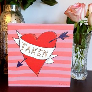A Valentine'sDay card with a big hand drawn heart with an arrow through it and a scroll with Taken on it.