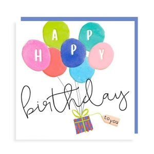 A birthday card in strong vibrant colours with embossing. With a present being carried off by a bunch of balloons with the words Happy birthday to you