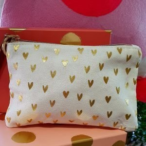 A cream canvas pouch covered in small gold hearts