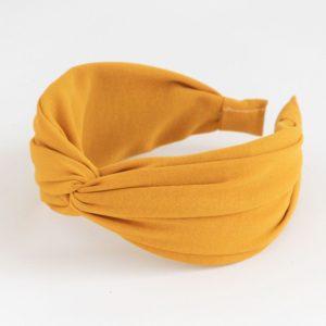 A bright yellow twist material hairband from British designer Caroline Gardner.