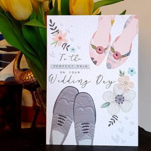 A beautiful embossed wedding card with a pair of men's shoes and ladie's shoes and delicate flowers and the words To the perfect pair on your wedding day.