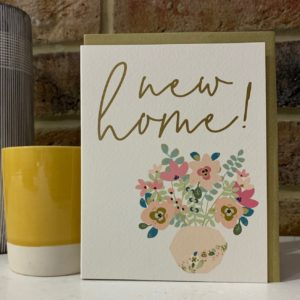 A small card with an image of a vase of flowers and the wording New Home printed on it.