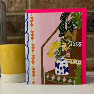 A card which has no wording so is a blank card with an image of flowers and plants on some stairs. The card is very colourful.