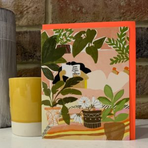 A blanks greetings card with an image of a woman reading a book called How many plants is enough, surrounded by house plants.