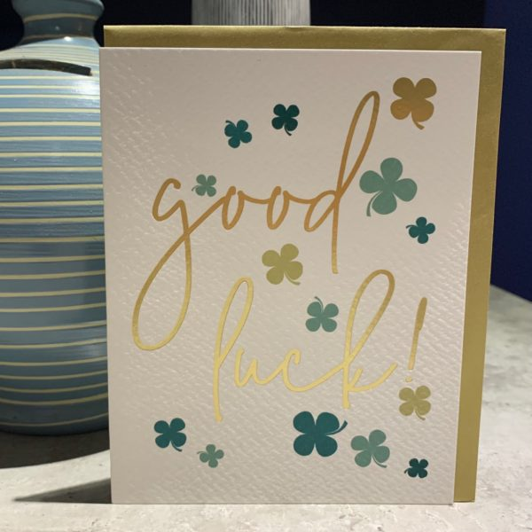 A card with the words Good Luck printed on it and lots of different coloured green four leaf clovers printed around the wording,
