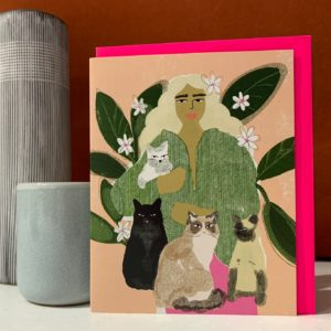 A card with an image of a woman with long fair hair surrounded by cats, The card is called Cat Lady and is left blank for the customers own message.