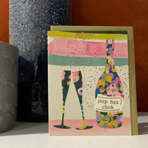 A card with an image of a bottle of prosecco and 2 glasses with the words pop fizz clink printed on the bottle.