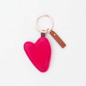 A brightly coloured pink heart shaped keyring with a gold coloured ring and a leather tab, from design company Caroline Gardner.