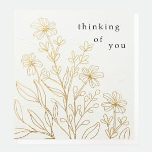 A white card with the words Thinking of You printed on it. The card has a botanical design emnpssed and printed in a gold foil detail.