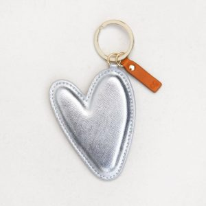 An extra large silver vegan leather heart shaped keyring, with a gold ring and leather tag.