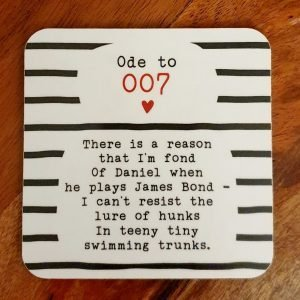 A melamine corked backed coaster with a fun poem about 007, Daniel Craig. There is a reason that I'm fond. Of Daniel when he plays James Bond, I can't resist the lure of hunks, In teeny tiny swimming trunks.
