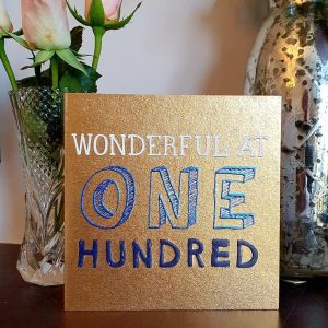 A metallic gold card with blue and white print with wonderful one hundred.