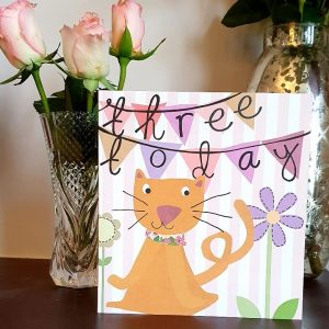 A lovely 3rd birthday card from Caroline Gardner with a drawing of a cute cat and a background of bunting and flowers with the words three today