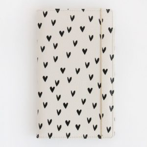 A lovely vegan leather travel wallet from designer Caroline Gardner. A white wallet covered in black hearts with an elasticated holder. The travel wallet has organiser sections on the inside.
