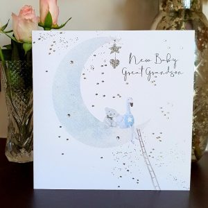 A large square card with an illustration of a half moon with a teddy and a duck sitting in it in blue colours. There are lots of silver foil tiny stars and the words new baby Grandson