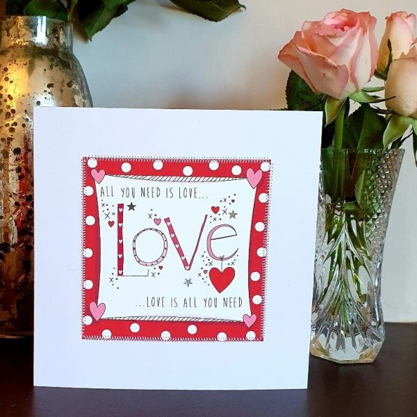 A valentines day card in red and white with the words All You Need Is Love, Love IS All You Need hand finished with little silver stars and hand stitching.