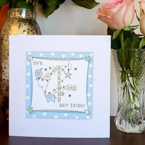 A 1st birthday card in blues with a little elephant holding a bunch of balloons in his trunk and a big one. Hand finished with stitching and silver stars